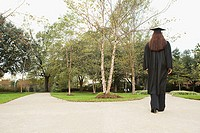 Female graduate walking down a path