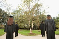 Female graduates walking down paths