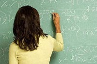 Female student writing on blackboard