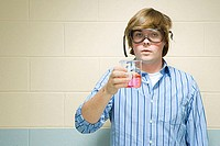 Male student holding chemical in flask