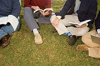 Four students sat reading outdoors