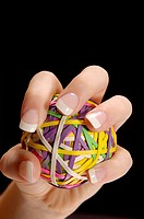 Manicured female had with long fingernails, gripping a rubberband ball as if squeezing or pitching a ball.  Black backround.  Room for text/ copy.  Fi...