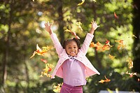 Portrait of girl throwing fall leaves in air