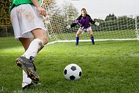 Girl kicking soccer ball toward goal