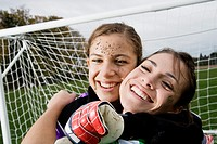 Two girls hugging in front of soccer net