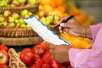 Woman´s hands with grocery list in produce department