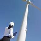 Female engineer examining wind turbine