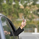 Businesswoman holding her cell phone out car window