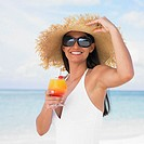 Woman having tropical drink at the beach (thumbnail)