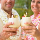Couple toasting each other with tropical drinks
