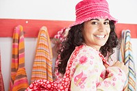 Young woman wearing a hat and shoulder bag smiling for the camera
