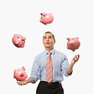 Businessman juggling piggy banks