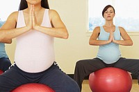 Pregnant women meditating on exercise balls
