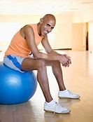 Middle aged man sitting on an exercise ball