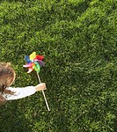 High angle view of girl picking up windmill toy