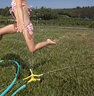 Young girl playing in the sprinkler