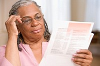 Senior adult woman reading papers