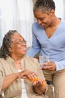 Daughter giving senior adult mother her medication