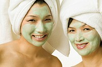 Young woman and her mother smiling for the camera in face masks