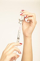 Woman with painted nails using a syringe