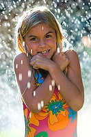 Portrait of a girl smiling in water sprinkler (thumbnail)
