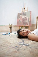 Young woman lying on the floor by a painting