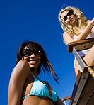 Low angle view of two young women on the beach (thumbnail)