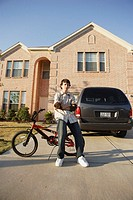 Teenage boy posing for the camera by his bike