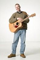 Man with acoustic guitar, posing in studio, portrait