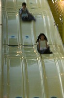 Two children (6-7) going down slide at amusement park