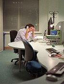 Man sitting at desk in office using telephone, resting head on hand