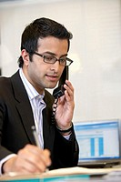 Young businessman taking notes while talking on telephone