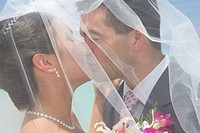 Bride and groom kissing under veil on beach, side view