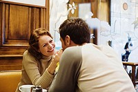 Couple in cafe holding hands across table, smiling, close-up