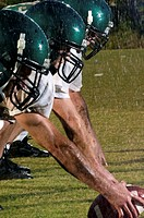 Three football players at line of scrimmage in rain, night, side view