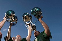 Four male football players holding helmets above heads, low angle view