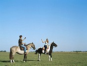 Young man and woman riding horses, man photographing woman, side view