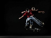 Young man and teenage boy (15-17) performing jumps on skateboards