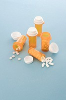 Prescription bottles and pills on blue background