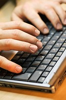 Close-up of a person's fingers using a laptop