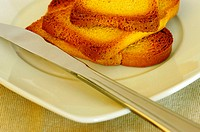 Close-up of slices of toast in a plate with a butter knife