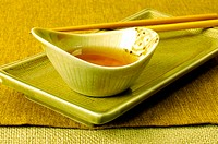 Close-up of soy sauce in a bowl with a pair of chopsticks
