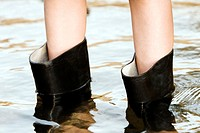 Low section view of a person wearing rubber boots (thumbnail)