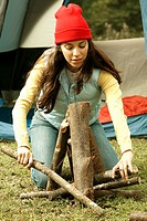 Close-up of a young woman adjusting firewood