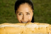 Portrait of a young woman holding a loaf of bread