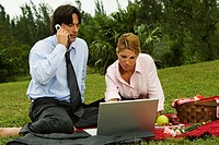 Close-up of a businessman and a businesswoman working on a laptop in the park