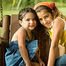 Portrait of two sisters sitting on a swing