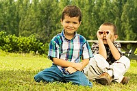 Portrait of two boys sitting on the lawn