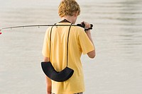 Rear view of a teenage boy holding a fishing rod