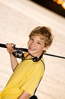 Portrait of a boy smiling carrying a fishing rod